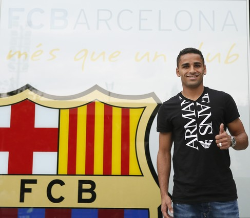 Brazilian soccer player Douglas gives a thumbs-up next to an FC Barcelona crest at the club's offices in Barcelona